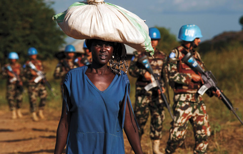 A displaced woman carries goods as United Nations Mission in South Sudan (UNMISS) peacekeepers patrol outside the premises of the UN Protection of Civilians (POC) site in Juba (October 4, 2016). © 2016 Albert González Farran/Getty Images.