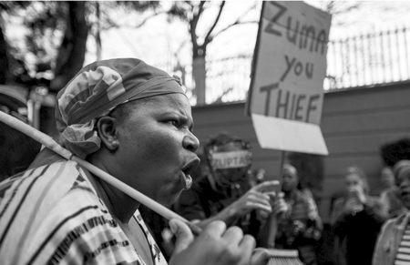 Demonstrators protesting against South African President Jacob Zuma and calling for his resignation hold placards and shout slogans outside the Gupta Family compound in Johannesburg on April 7, 2017.