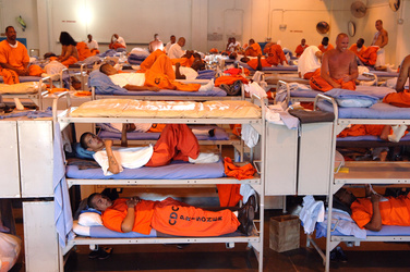 Prisoners sleeping in triple bunk beds stuffed into large room
