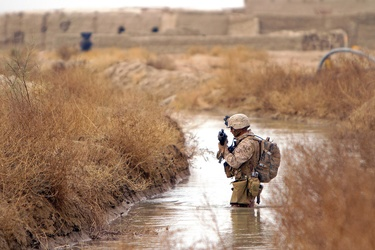 American soldier crosses stream in Afghanistan in 2011
