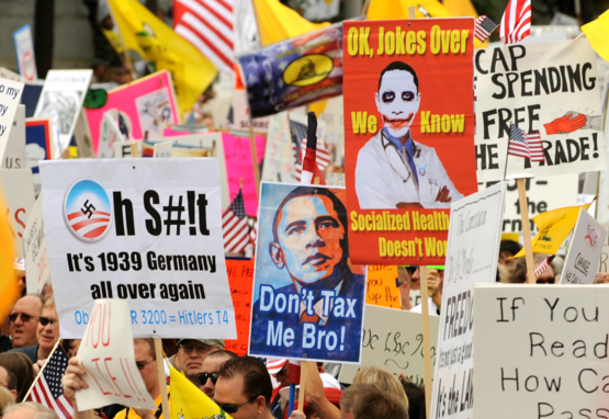 Reactionaries hold signs protesting President Barack Obama's health care legislation