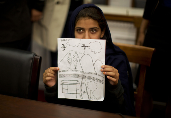 Pakistani girl shows drawing of a drone bombing