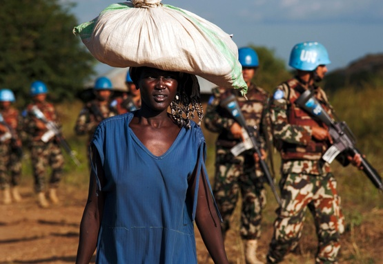 African woman carries bag on her head while UN peacekeepers patrol the background