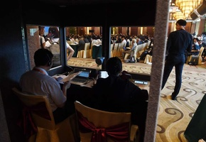 Translators work in a booth as delegates listen to speeches during the opening session of the Belt and Road Forum on Legal Cooperation in Beijing on July 2.